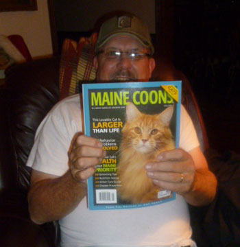 Daddy holds his copy of Cat Fancy magazine dedicated to Maine Coons.